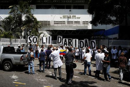 """Venezuelans, including doctors, hold banners that read """"Solidarity"""" as they gather outside a public children hospital during an ongoing blackout in Caracas, Venezuela March 10, 2019. REUTERS/Marco Bello"""