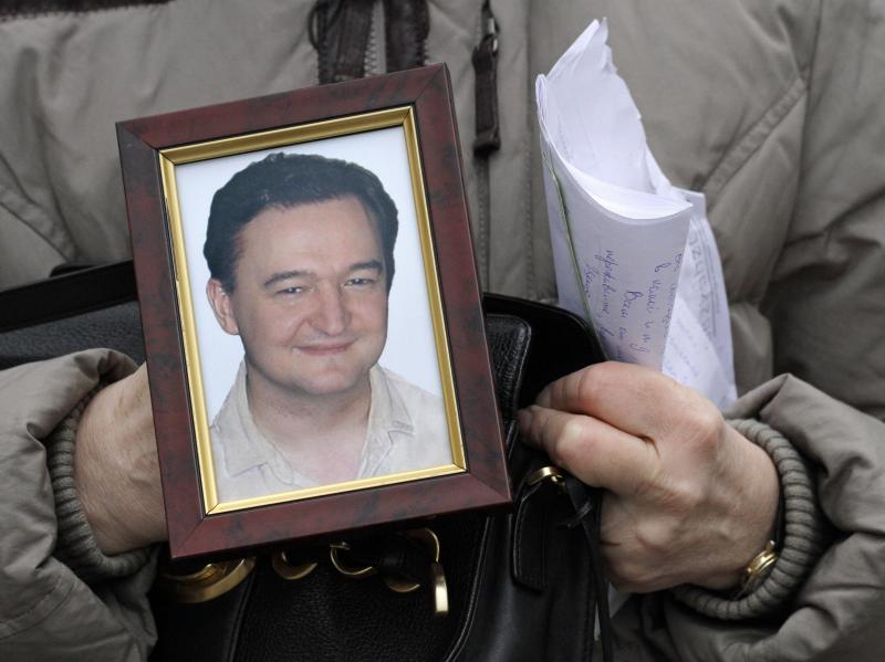 FILE In this Monday, Nov. 30, 2009, file photo a portrait of lawyer Sergei Magnitsky who died in jail, is held by his mother Nataliya Magnitskaya, as she speaks during an interview with the AP in Moscow. The Senate is taking up legislation Wednesday, Dec. 5, 2012, that would end four-decade-old trade restrictions that are blocking U.S. businesses from enjoying the benefits of a more-open Russian market. Russian news agencies say on Thursday that a court in Moscow has found dead lawyer Sergei Magnitsky guilty of tax evasion, concluding an unusual posthumous trial. Magnitsky died in prison of untreated pancreatitis in 2009, months after alleging that organized criminals colluded with corrupt Interior Ministry officials to claim a $230 million tax rebate through illegally obtained subsidiaries of Browder's Hermitage Capital investment company. (AP Photo/Alexander Zemlianichenko, File)