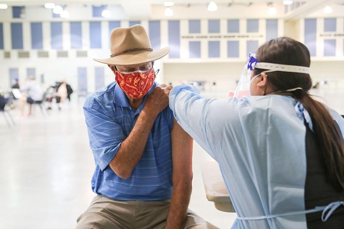 Barry Parkins of Indian Wells receives a COVID-19 vaccination from Jennifer Salazar, R.N. at the Riverside County Fairgrounds in Indio, January 17, 2021.