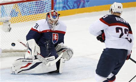 Team USA's Brown scores on Slovakia's goalie Budaj during the second period of their men's preliminary round ice hockey game at the 2014 Sochi Winter Olympics