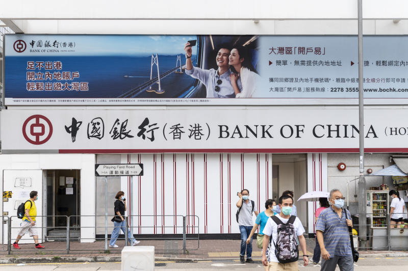 HONG KONG, CHINA - 2020/07/17: Pedestrians wearing face masks walk past a Chinese state-owned commercial banking company Bank of China branch in Hong Kong. (Photo by Budrul Chukrut/SOPA Images/LightRocket via Getty Images)