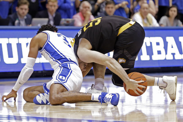 Duke guard Tre Jones, left, and Winthrop guard Chandler Vaudrin scramble for the ball during the first half of an NCAA college basketball game in Durham, N.C., Friday, Nov. 29, 2019. (AP Photo/Gerry Broome)