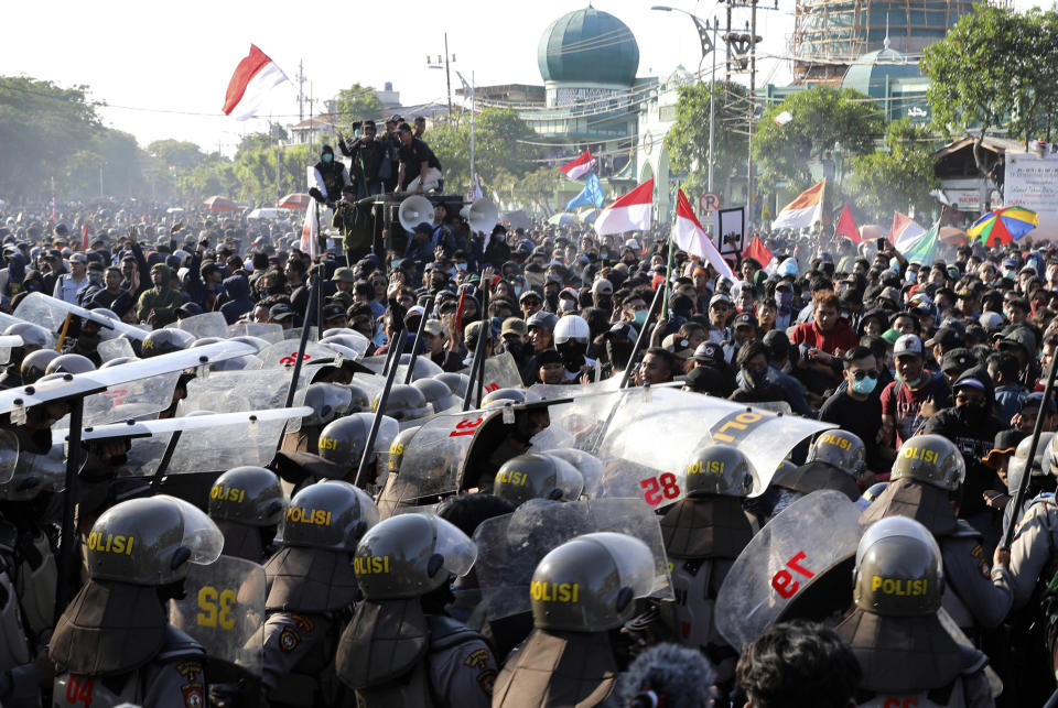Riot police officers block students from advancing towards the local parliament during a rally in Surabaya, East Java, Indonesia, Thursday, Sept. 26, 2019. Protests continue in several cities in the country as students rallied against a new law that critics say cripples the country's anti-corruption agency. (AP Photo/Trisnadi)