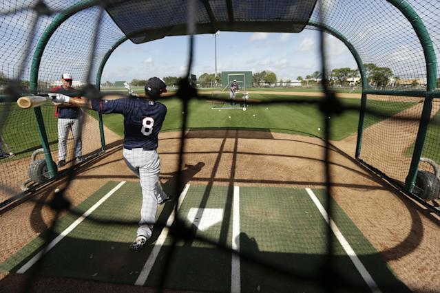 Minnesota Twins catcher Kurt Suzuki takes batting practice during spring training baseball practice Friday, Feb. 21, 2014, in Fort Myers, Fla. (AP Photo/Steven Senne)