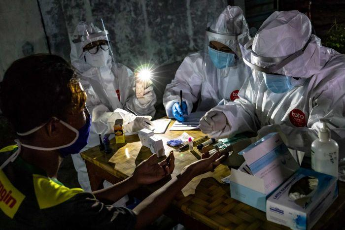 Three health workers in PPE conduct a test on a man under the light of an iphone torch