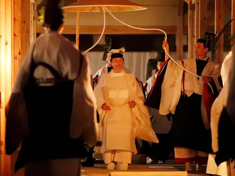 Japan's Emperor Naruhito walks towards one of two main halls of the shrine for Daijosai, or great thanksgiving festival, at the Imperial Palace in Tokyo, Thursday 14 November 2019: AP
