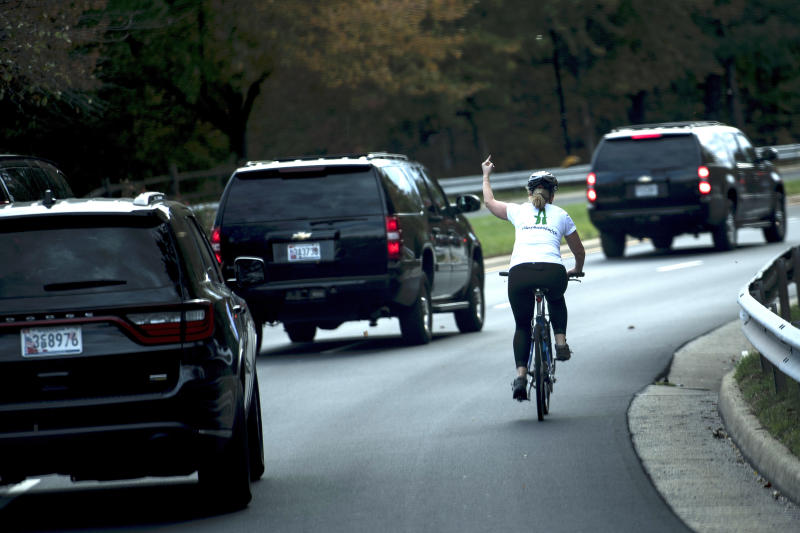 A female cyclist lets the White House know how she feels about the Trump administration as the president's motorcade passes by.