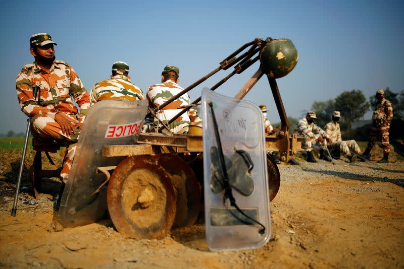 Policemen sit on a cultivator at the site of a protest against new farm laws, at a state border on a national highway, in Shahjahanpur