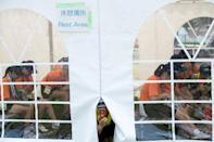 People rest inside a cooling tent during the beach volleyball test event for the Tokyo Olympics