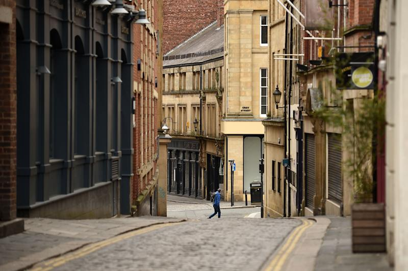 A man walks through a near-deserted centre of Newcastle upon Tyne at Thursday lunchtime in north-east England on April 9, 2020 as Britain continued to battle the outbreak of new coronavirus and the governement prepared to extend the nationwide lockdown. - The disease has struck at the heart of the British government, infected more than 60,000 people nationwide and killed over 7,000, with another record daily death toll of 938 reported on April 8. A testing centre opened in Gateshead on April 9, 2020 as the government ramped up its testing of NHS staff for the new coronavirus. (Photo by Oli SCARFF / AFP) (Photo by OLI SCARFF/AFP via Getty Images)