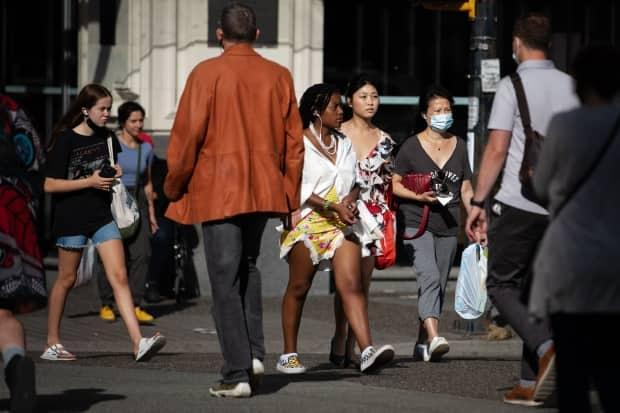 Pedestrians cross a busy intersection in Vancouver on Tuesday, Aug.10, 2021.  (Maggie MacPherson/CBC - image credit)