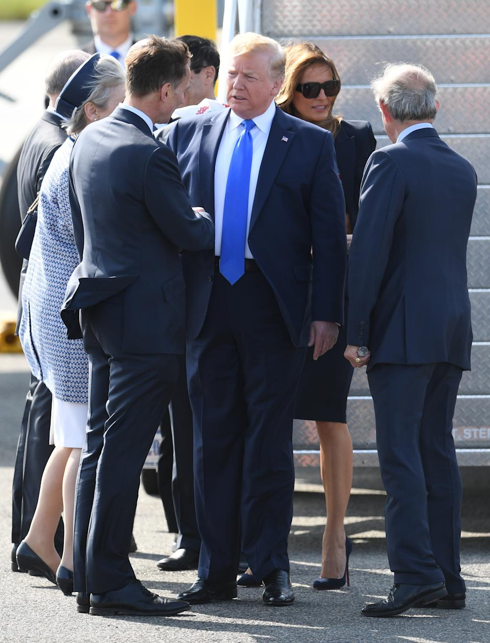 Touching down: President Trump shakes hands with Foreign Secretary Jeremy Hunt on the runway at Stansted.