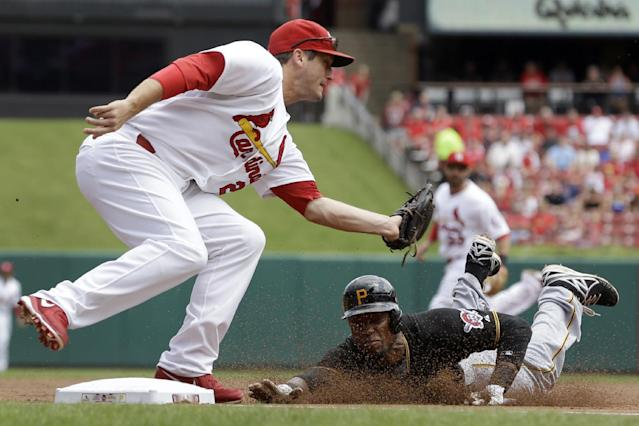 St. Louis Cardinals third baseman David Freese, left, prepares to tag out Pittsburgh Pirates' Starling Marte on an attempted steal during the first inning of a baseball game Thursday, Aug. 15, 2013, in St. Louis. (AP Photo/Jeff Roberson)
