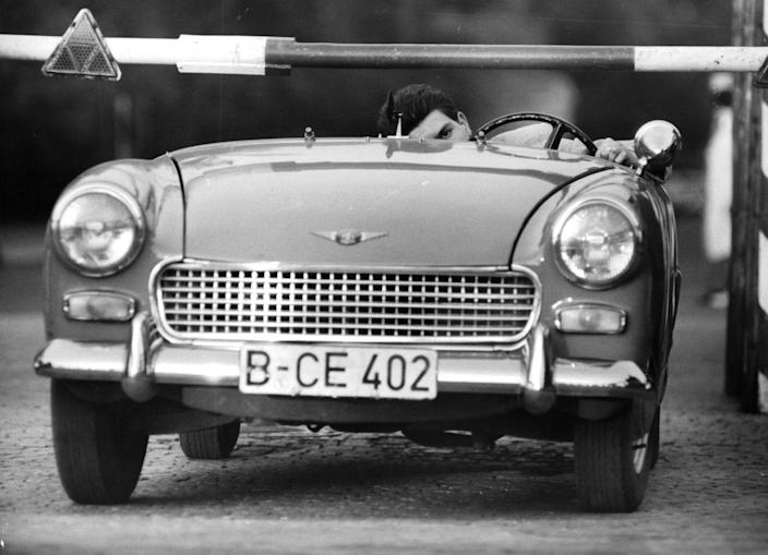 """<p>In May 1963, Austrian <a href=""""http://www.mossmotoring.com/sprite-true-love-cold-war/"""" rel=""""nofollow noopener"""" target=""""_blank"""" data-ylk=""""slk:Heinz Meixner drove up to Checkpoint Charlie"""" class=""""link rapid-noclick-resp"""">Heinz Meixner drove up to Checkpoint Charlie</a> in a fancy British sports car, a bright red Austin Healey Sprite convertible. The top was down, and Meixner had made one important modification to the car: he <a href=""""https://rarehistoricalphotos.com/heinz-meixner-defect-removing-windshield-1963/"""" rel=""""nofollow noopener"""" target=""""_blank"""" data-ylk=""""slk:removed the windshield"""" class=""""link rapid-noclick-resp"""">removed the windshield</a>. When the border guards ordered him to pull over for inspection, Meixner lay flat and hit the accelerator. Without the windshield, the entire car was low enough to slip under the lowered barrier. Meixner made it across—along with his East German fiancée hiding behind the seat and his prospective mother-in-law in the trunk. </p><p>Norbert Konrad pulled off the same trick a few months later in the exact same car, but the East Germans then added steel bars under the barrier arm to prevent a third attempt.</p>"""