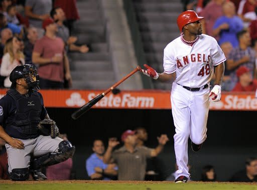 Los Angeles Angels' Torii Hunter, right, drops his bat as he hits a two-run home run as Seattle Mariners catcher Miguel Olivo looks on during the fifth inning of their baseball game against the Seattle Mariners, Tuesday, Sept. 25, 2012, in Anaheim, Calif. (AP Photo/Mark J. Terrill)