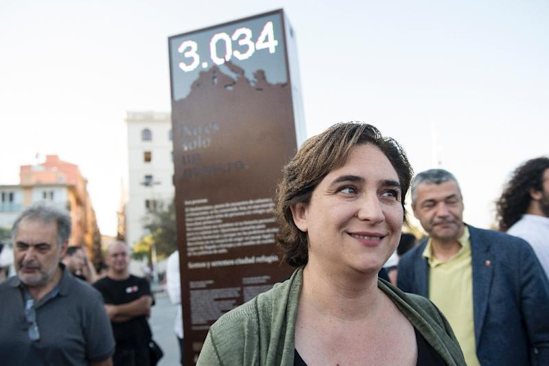 """Barcelona's Mayor Ada Colau poses in front a digital billboard that shows the number of refugees who have died in the Mediterranean sea, named """"the shame counter"""" (AFP Photo/Josep Lago)"""