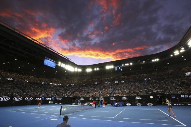 The sun sets behind Melbourne Park as Petra Kvitova, right, of the Czech Republic hits a forehand to Japan's Naomi Osaka during the women's singles final on Rod Laver Arena at the Australian Open tennis championships in Melbourne, Australia, Saturday, Jan. 26, 2019. (AP Photo/Aaron Favila)