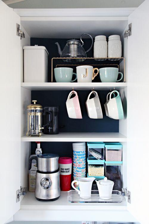 """<p>It's amazing what a difference some dark paint makes when trying to find items. Plus, hooks attached to the bottom of a shelf allows mugs to hang, while dividers create shorter shelves for even more coffee cups.</p><p><em><a href=""""http://www.iheartorganizing.com/2015/11/organized-coffee-cabinet.html"""" rel=""""nofollow noopener"""" target=""""_blank"""" data-ylk=""""slk:See more at I Heart Organizing »"""" class=""""link rapid-noclick-resp"""">See more at I Heart Organizing »</a></em></p><p><strong>What you'll need: </strong><span class=""""redactor-invisible-space"""">shelf riser, $10 for a 2-pack, <a href=""""https://www.amazon.com/Evelots-Kitchen-Shelves-Cabinet-Storage/dp/B01HQM1MME/?tag=syn-yahoo-20&ascsubtag=%5Bartid%7C2139.g.36060899%5Bsrc%7Cyahoo-us"""" rel=""""nofollow noopener"""" target=""""_blank"""" data-ylk=""""slk:amazon.com"""" class=""""link rapid-noclick-resp"""">amazon.com</a></span><br></p>"""