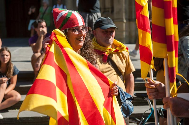 A woman with a Basque flag on her head holds a Catalonian flag, at a demo in San Sebastian in support of Catalonia and its planned referendum on independence from Madrid