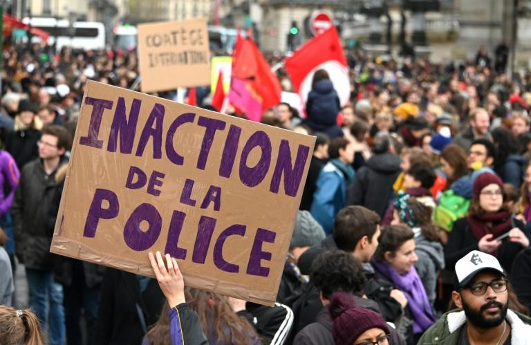 """A person holds up a placard reading """"Police inaction"""""""