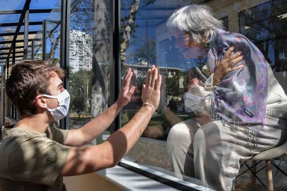 A teenager speaks with his 81-year-old grandmother through a window at a hospital.