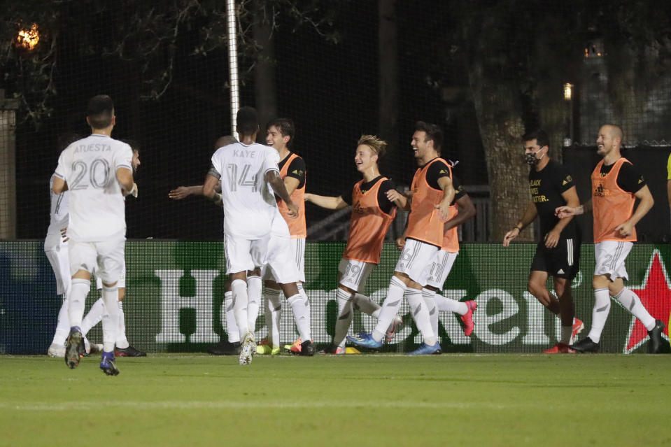 Los Angeles FC players celebrate after a goal during the second half of an MLS soccer match, Friday, July 31, 2020, in Orlando, Fla. (AP Photo/John Raoux)