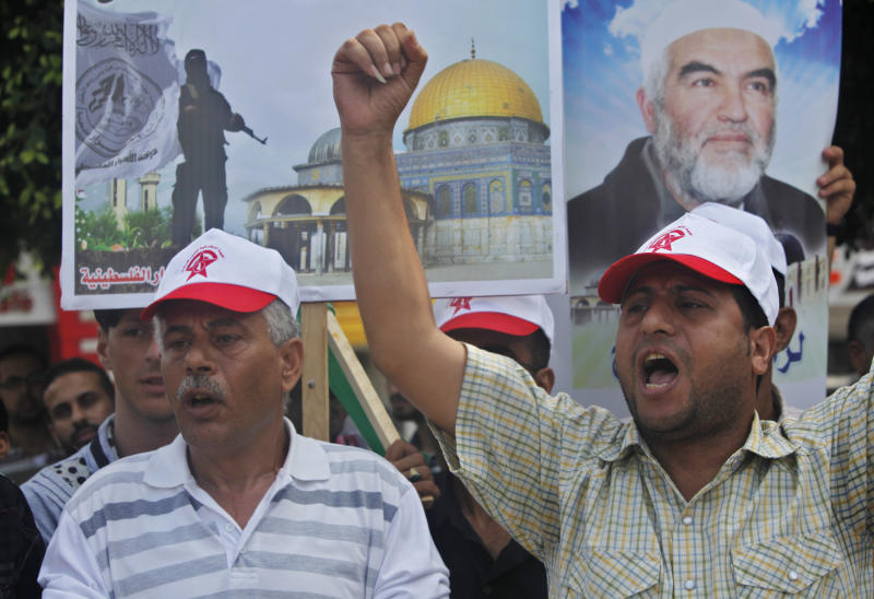 Palestinians chant anti-Israeli slogans as others hold a picture of Sheik Raed Salah, the leader of the Islamic Movement in Israel, during a protest to condemn what protesters claim was a desecration of Al-Aqsa Mosque in Jerusalem by Jewish extremists, in Gaza City, Wednesday, Sept. 4, 2013. Israeli police spokesman Micky Rosenfeld says that clashes in Jerusalem erupted Wednesday when some 300 Palestinian demonstrators tried to block a group of visitors from reaching the sensitive hilltop compound revered by both Jews and Muslims. Israeli police arrested seven Palestinians after clashes between stone-throwing demonstrators and Israeli security forces. (AP Photo/Adel Hana)