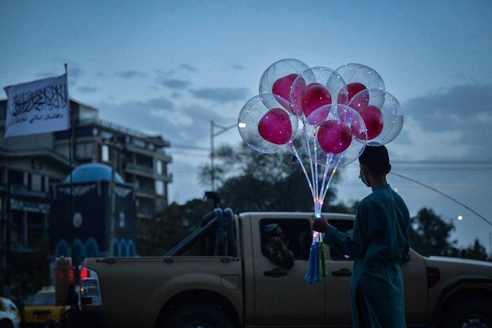 An Afghan boy stands along a road holding a bunch of balloons to sell in Kabul on Monday (AFP/Getty)