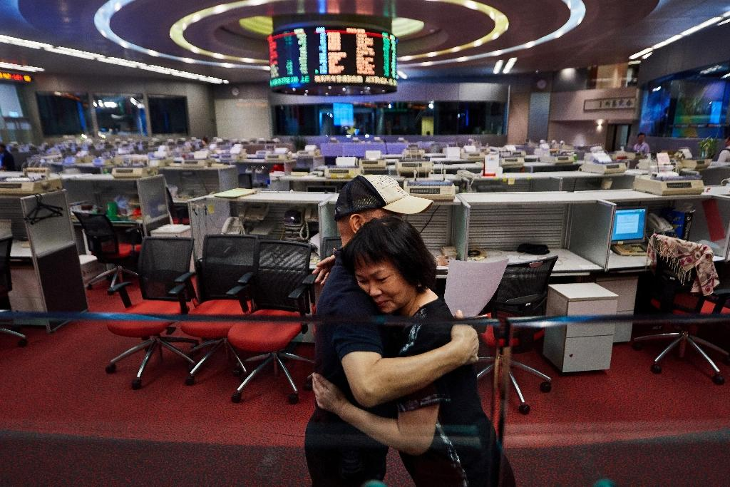 With just a handful of brokers left on the floor following the move to electronic trading, the Hong Kong Stock Exchange's historic trading hall will close at the end of the month (AFP Photo/Anthony WALLACE)