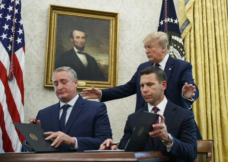 President Donald Trump, walks to acting Department of Homeland Security Secretary Kevin McAleenan, seated right, and Guatemalan Interior Minister Enrique Degenhart in the Oval Office of the White House in Washington, Friday, July 26, 2019. Trump announced that Guatemala is signing an agreement to restrict asylum applications to the U.S. from Central America. (AP Photo/Carolyn Kaster)
