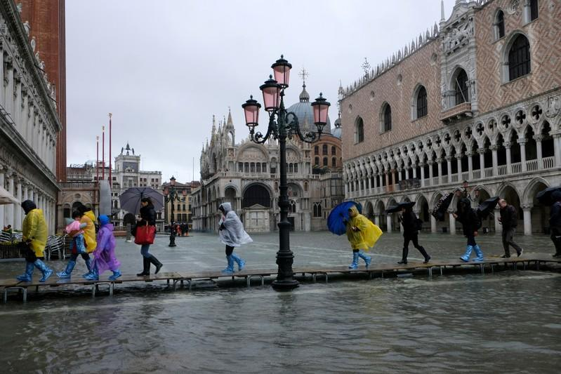 People walk on a catwalk in the flooded St. Mark's Square in Venice, Italy