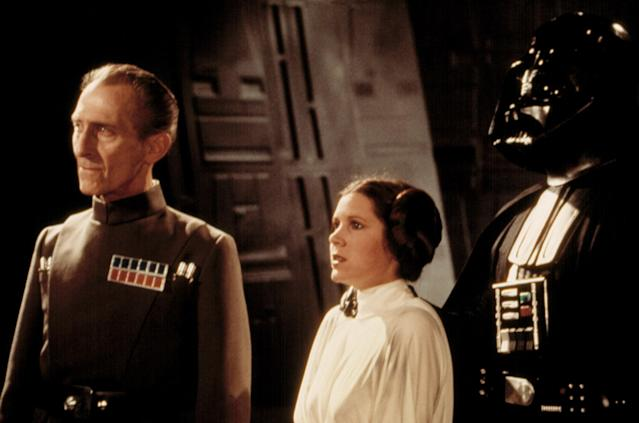 "Peter Cushing as Grand Moff Tarkin and Carrie Fisher as Princess Leia in <i>Star Wars</i> (1977). Fisher's brother, Todd, told Yahoo Entertainment that she ""freaked out"" when she saw they included a scene in which she uses a British accent. (Photo: Everett Collection)"