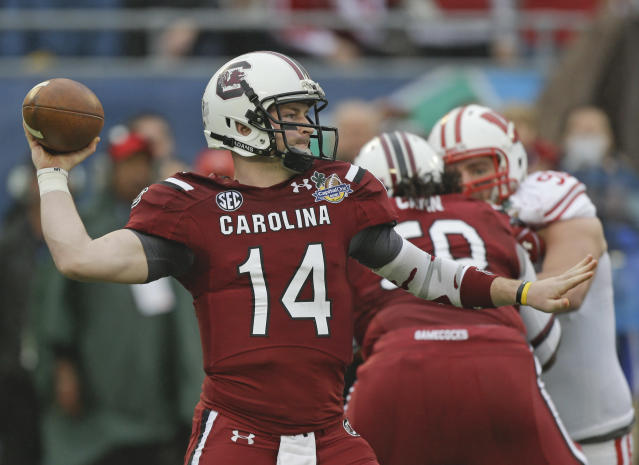South Carolina quarterback Connor Shaw (14) throws a pass as he is rushed by Wisconsin defensive end Pat Muldoon, right, during the first half of the Capital One Bowl NCAA college football game in Orlando, Fla., Wednesday, Jan. 1, 2014.(AP Photo/John Raoux)