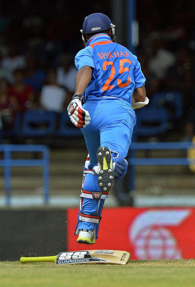 Indian cricketer Shikhar Dhawan drops his bat as he takes a run during the fourth match of the Tri-Nation series between India and West Indies at the Queen's Park Oval in Port of Spain on July 5, 2013. West Indies won the toss and elected to field. AFP PHOTO/Jewel Samad        (Photo credit should read JEWEL SAMAD/AFP/Getty Images)