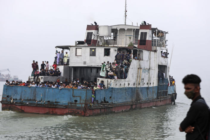 Thousands of people leaving for their native places to celebrate Eid-al-Fitr crowd a ferry at the Mawa terminal ignoring risks of coronavirus infection in Munshiganj, Bangladesh, Thursday, May 13, 2021. (AP Photo/Mahmud Hossain Opu)