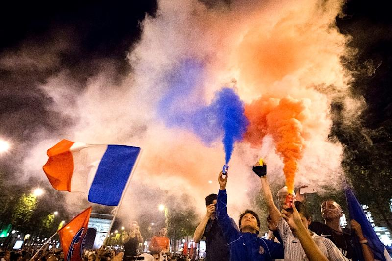 France supporters celebrate with  flares after France won the Euro 2016 semi-final football match against Germany, on the Champs Elysees in Paris on July 7, 2016
