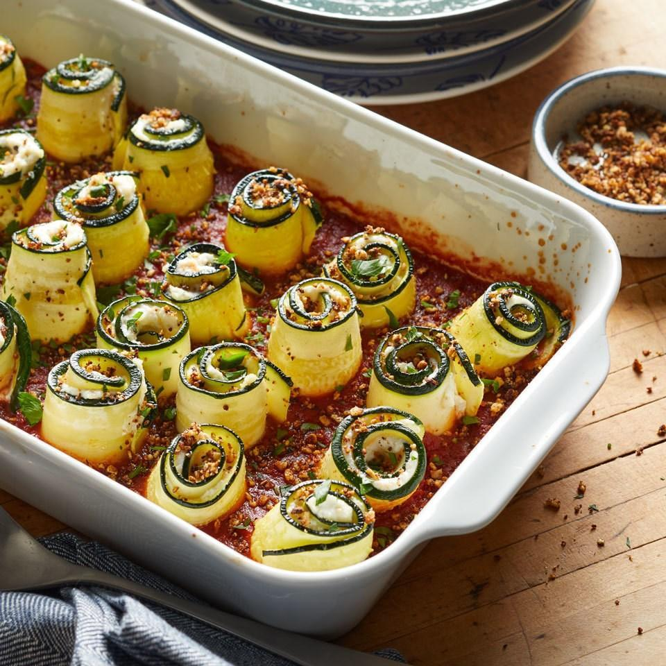 """<p>Give lasagna rolls a healthy low-carb makeover with this easy recipe that subs in thinly sliced zucchini for lasagna noodles. Finish off this cheesy vegetarian casserole with a crispy breadcrumb topping made from almonds to keep it gluten-free. <a href=""""https://www.eatingwell.com/recipe/261689/zucchini-lasagna-rolls/"""" rel=""""nofollow noopener"""" target=""""_blank"""" data-ylk=""""slk:View Recipe"""" class=""""link rapid-noclick-resp"""">View Recipe</a></p>"""