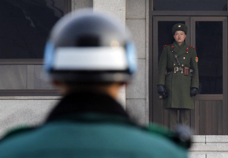 FILE - In this Dec. 28, 2011 file photo, a North, right, and a South Korean soldier look at each other's sides at the Panmunjom (DMZ) that separates the two Koreas since the Korean War, in Paju, South Korea. A North Korean soldier killed two of his superiors Saturday, Oct. 6, 2012, and defected to South Korea across the countries' heavily armed border in a rare crossing that prompted South Korean troops to immediately beef up their border patrol, officials said. The soldier shot his platoon and squad leaders before crossing the western side of the Demilitarized Zone at around noon, a Defense Ministry official said, citing the soldier's statement after he was taken into custody by South Korean border guards. (AP Photo/Kim Kyung-hoon, Pool)
