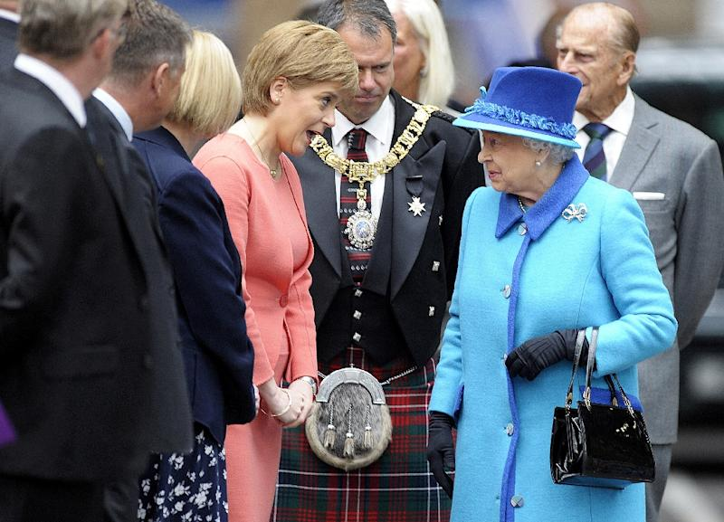 Queen Elizabeth speaks with Scottish First Minister Nicola Sturgeon as she arrives at Edinburgh's Waverley Station, on September 9, 2015