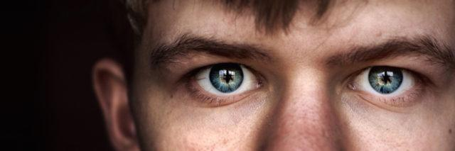 Close up of a young man with piercing blue eyes