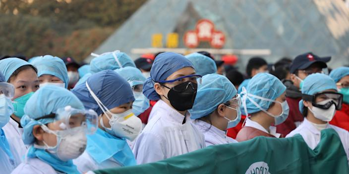 Medical staff rally before taking over a temporary hospital in an exhibition center in Wuhan, Hubei province, on February 5, 2020.