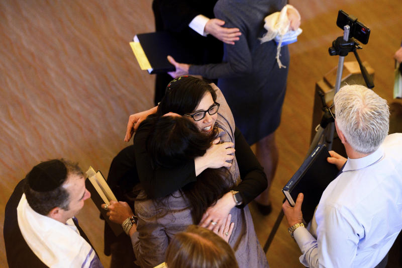 In this Saturday, Feb. 1, 2020, photo, Rabbi Jacqueline Mates-Muchin hugs a worshipper during Shabbat morning service at Temple Sinai in Oakland, Calif. Mates-Muchin says there's extra worry as she feels obliged to be constantly mindful of her congregation's safety. (AP Photo/Noah Berger)
