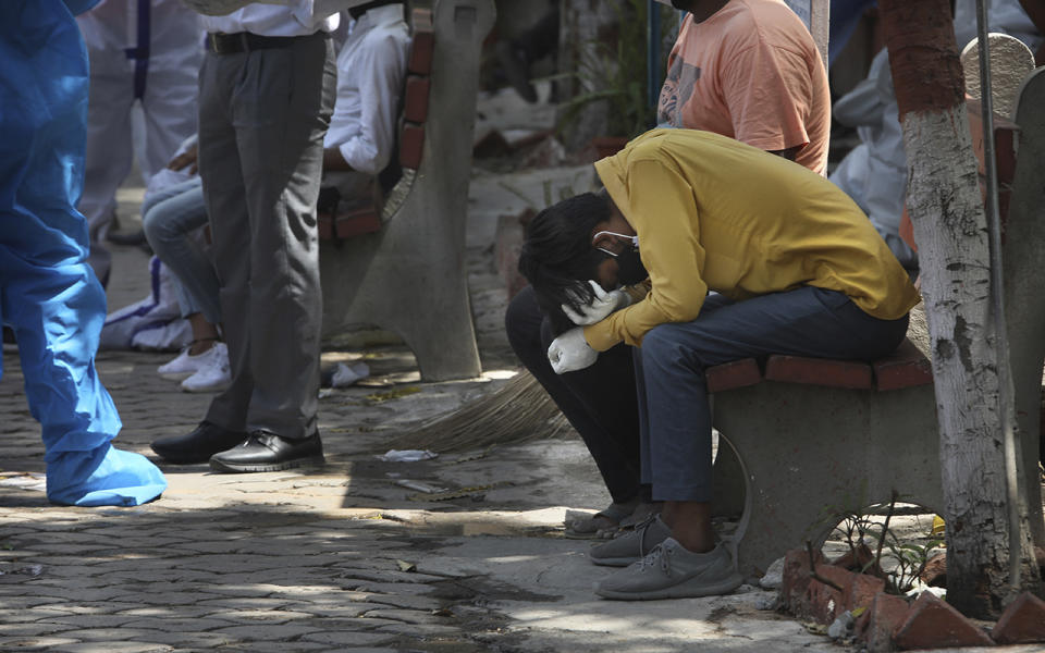 A man in yellow lowers his head while sat on a street bench in desperation amid a vaccine shortage.