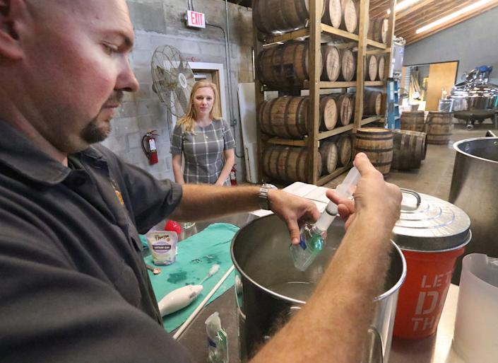 Copper Bottom Craft Distillery owner Jeremy Craig fills a small bottle with hand sanitizer while his wife and co-owner Jenni Craig looks on, Wednesday March 18, 2020 as the Holly Hill, Florida, distillers use some of their product to make hand sanitizer and give it away to those in the community during the Coronavirus outbreak.