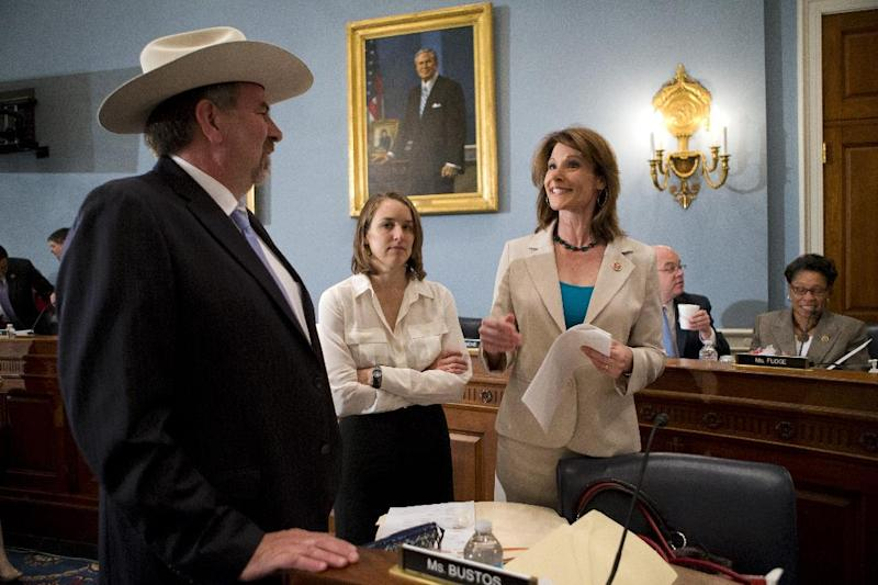 House Agriculture Committee members, Rep. Doug LaMalfa, R-Calif., left, speaks with Rep. Cheri Bustos, D-Ill., right, on Capitol Hill in Washington, Wednesday, May 15, 2013, prior to the start of the committee's hearing to consider proposals to the 2013 Farm Bill, including small cuts to the $80 billion-a-year food stamp program in an effort to appease conservatives who say the food aid has become too expensive. At center is unidentified aide. (AP Photo/J. Scott Applewhite)