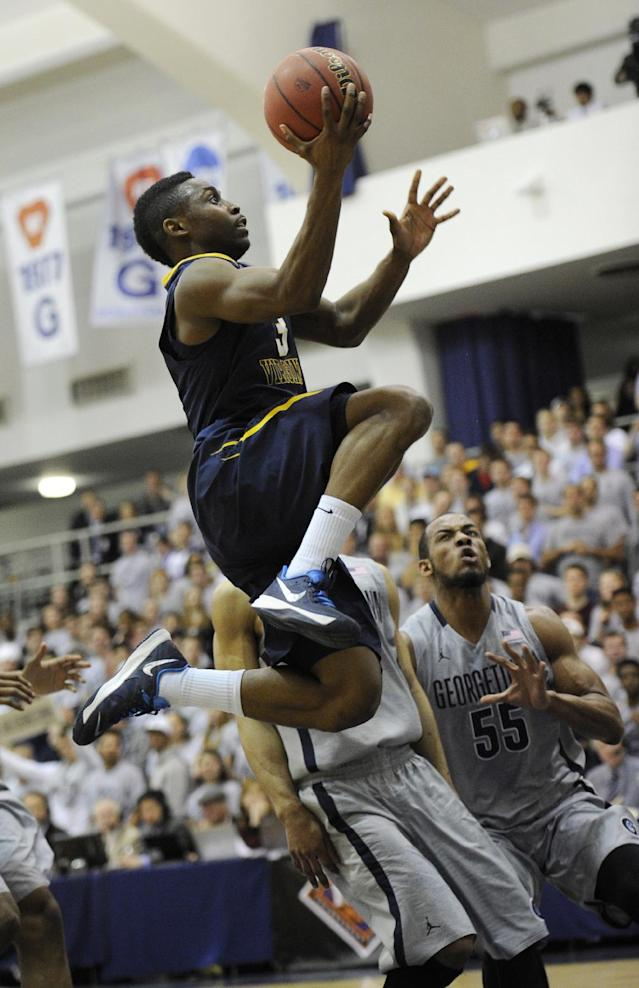 West Virginia guard Juwan Staten (3) goes to the basket against Georgetown guard Jabril Trawick (55) during the first half of an NCAA college NIT tournament first round basketball game, Tuesday, March 18, 2014, in Washington. (AP Photo/Nick Wass)