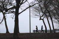 Two runners get in their last legs of exercise before a Chicago police officer notifies them that the trails along Lake Michigan are closed in an effort to limit the spread of COVID-19 infections, Thursday, March 26, 2020, in Chicago. The new coronavirus causes mild or moderate symptoms for most people, but for some, especially older adults and people with existing health problems, it can cause more severe illness or death. (AP Photo/Charles Rex Arbogast)