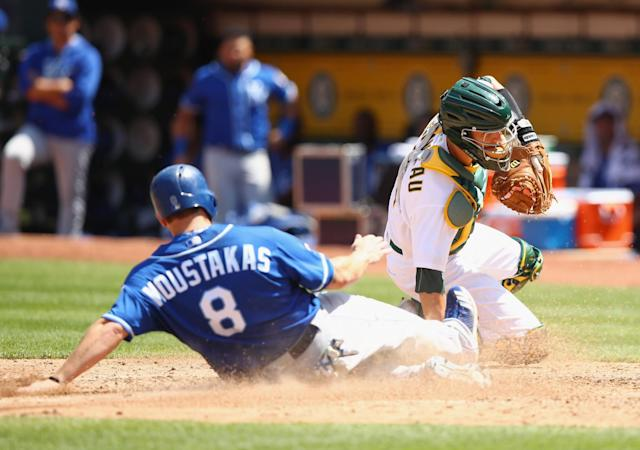 <p>OAKLAND, CA – AUGUST 16: Mike Moustakas #8 of the Kansas City Royals slides safely into home plate past catcher Dustin Garneau #12 of the Oakland Athletics to score in the fifth inning at Oakland Alameda Coliseum on August 16, 2017 in Oakland, California. (Photo by Ezra Shaw/Getty Images) </p>