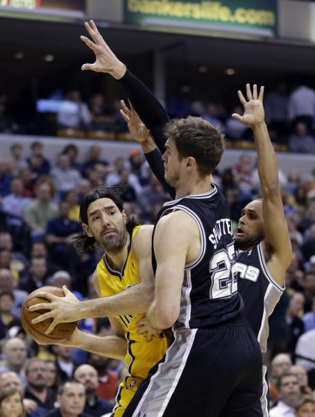 Indiana Pacers forward Luis Scola, left, is trapped by San Antonio Spurs center Tiago Splitter, center, and guard Patty Mills in the first half of an NBA basketball game in Indianapolis, Monday, March 31, 2014. (AP Photo/Michael Conroy)