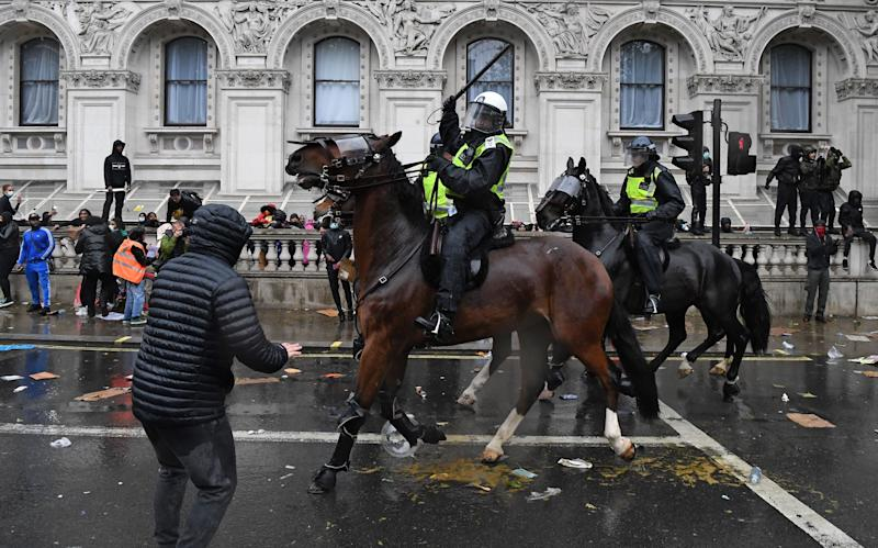A mounted police officer raises their baton as police horses ride along Whitehall in an attempt to disperse protesters. (Photo: DANIEL LEAL-OLIVAS via Getty Images)